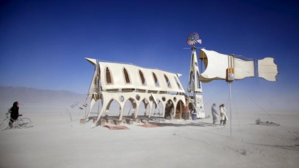 "Dust blows by the Prairie Wind Chapel art installation during the Burning Man ""Carnival of Mirrors"" arts and music festival in the Black Rock Desert of Nevada"